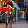 Happy kids walking the street under the rain — Stock Photo