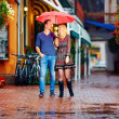 Happy couple walking under the rain — Stock Photo