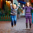 Happy kids jumping under the rain — Stockfoto