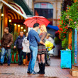 Couple in love standing under the rain on colorful street — Stock Photo #36945299