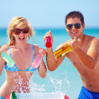 Stock Photo: Happy friends holding chilling drinks on beach