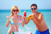 Happy friends holding chilling drinks on the beach — Stock Photo