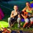 Happy teenagers singing songs around camp fire — Stock Photo