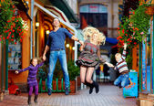 Happy family jumping on colorful street — Stock Photo