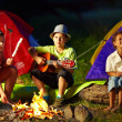 Happy teens around night campfire — Stock Photo