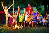 Laughing kids friends having fun around campfire — Stock Photo