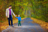 Father and son walking the autumn forest road — Stock Photo