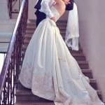 Gorgeous wedding couple kisses on stairs — Stock Photo