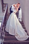 Gorgeous wedding couple kisses on stairs — Zdjęcie stockowe