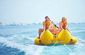 Happy people having fun on banana boat — Foto Stock