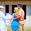 Young couple and architect discussing house project — Stock Photo #40305353