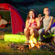 Happy kids roasting marshmallows around campfire — Stock Photo