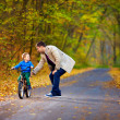 Stock Photo: Father teaches son to ride bicycle