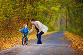 Father teaches son to ride the bicycle — Stock Photo