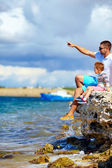 Father and son look into the distance, sitting on the cliff — Stock Photo