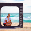 Family posing in tv frame on the beach — Stock Photo