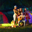 Happy teens together around camp fire — Stock Photo