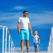 Stock Photo: Father and son on bridge, sky background