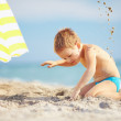 Happy boy playing in sand on the beach — Stock Photo