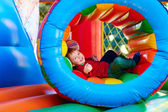 Happy kids playing on inflatable attraction playground — Stock Photo