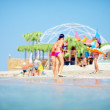 Group of people relaxing on summer beach — Stock Photo
