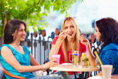 Pretty young girls sitting in summer cafe — Stock Photo