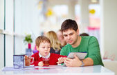 Father and son with tablet in colorful cafe — Stock Photo