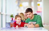 Vater und sohn mit tablet im bunten café — Stockfoto