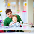 Father and son playing toys together in cafe — Stock Photo