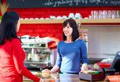 Waitress serves customer in coffee shop — Stock Photo