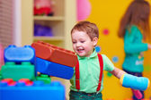Happy kid smashing toys in kindergarten — Stock Photo