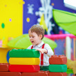 Cute kid playing with toys in nursery room — Stock Photo #43681145