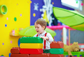Cute kid playing with toys in nursery room — Stock Photo