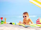Cute boy kid sunbathing on the beach — Stock Photo