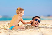 Happy kid helping father in sand talk on the mobile phone — Stock Photo
