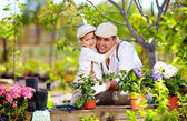 Happy family cares for plants in spring garden — Stock Photo