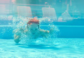 Happy kid dives underwater in the pool — Stock Photo