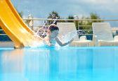 Cute boy kid having fun on water slide — Stock Photo