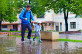 Happy father and son running under the rain — Stockfoto