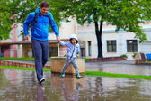 Happy father and son running under the rain — Stok fotoğraf