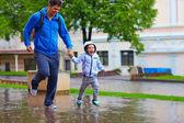 Feliz pai e filho correndo sob a chuva — Fotografia Stock