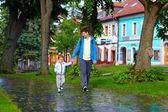 Ojciec i syn spacery ulicy po deszczu — Zdjęcie stockowe