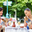 Beautiful girls with pets sitting in street cafe — Stock Photo #47978013