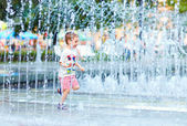 Excited boy running between water flow in city park — Stock Photo