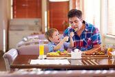 Boy feeding father in restaurant — Stock Photo