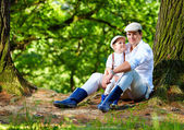 Father and son sitting under an old tree in forest — Stock Photo