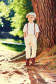 Cute boy near old tree in retro clothes — Stock Photo