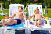 Teenage boys relaxing on sunbeds in waterpark — Stock Photo