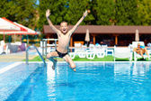 Excited teenage boy jumping in the pool — Stock Photo