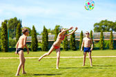 Group of teenage kids playing with ball on summer lawn — Stok fotoğraf